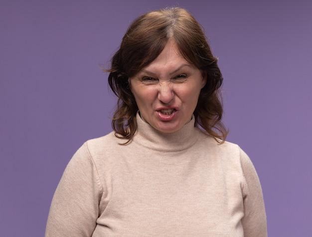 Frau mittleren alters in beigem rollkragenpullover mit wütendem gesicht, das über lila wand steht