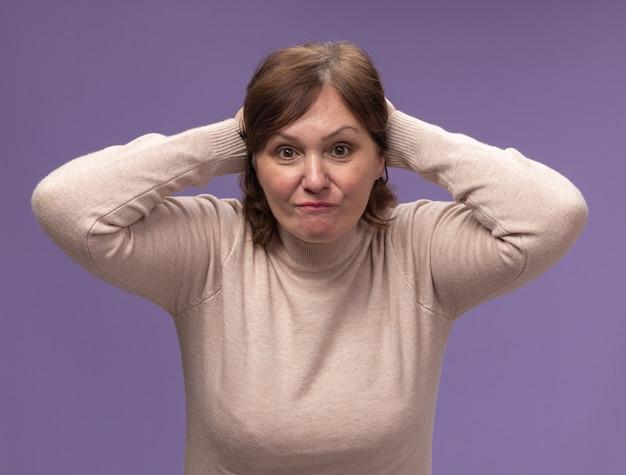 Frau mittleren alters in beigem rollkragenpullover verwirrt und unzufrieden mit den händen auf dem kopf wegen eines fehlers, der über der lila wand steht