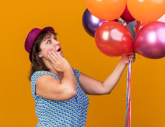 Frau mittleren alters in partyhut, die bunte luftballons hält und sie erstaunt und überrascht ansieht, wenn sie geburtstagsfeier über orangefarbener wand feiert
