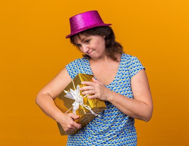 Frau mittleren alters in partyhut, die ein geschenk hält, das verwirrt aussieht, um die box zu öffnen, die geburtstagsfeier über oranger wand feiert