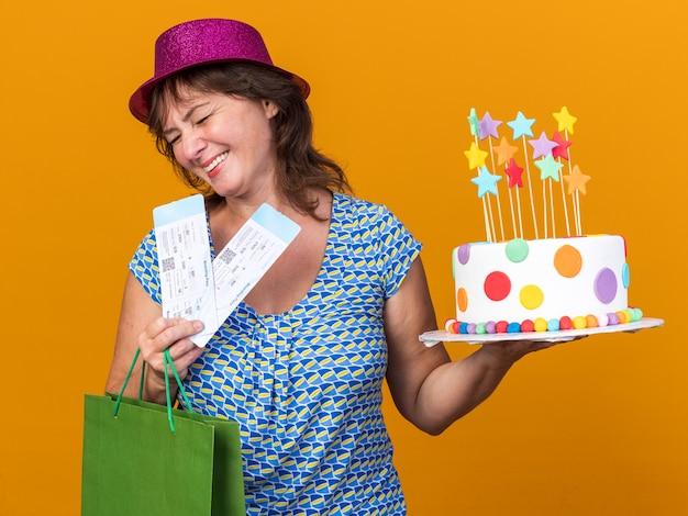 Frau mittleren alters in partyhut, die papiertüte mit geschenken hält, die geburtstagstorte und flugtickets halten, glücklich und erfreut lächelnd, fröhlich feiernd, geburtstagsfeier über orangefarbener wand stehend feiernd