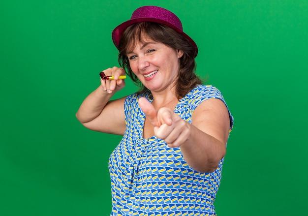 Frau mittleren alters in partyhut, die pfeife hält und mit dem zeigefinger zeigt, die fröhlich lächelt und die geburtstagsfeier feiert, die über grüner wand steht