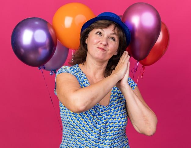 Frau mittleren alters in partyhut mit bunten luftballons, die handflächen zusammenhalten, glücklich und aufgeregt warten auf überraschung