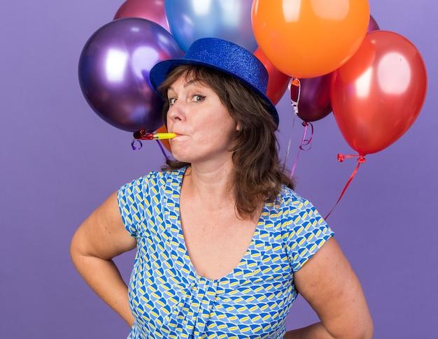 Frau mittleren alters in partyhut mit einem haufen bunter ballons, die fröhlich und fröhlich pfeifen