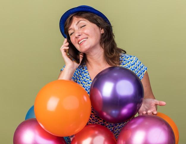 Frau mittleren alters in partyhut mit einem haufen bunter luftballons, die fröhlich lächeln, während sie auf dem handy telefoniert und die geburtstagsfeier über grüner wand feiert