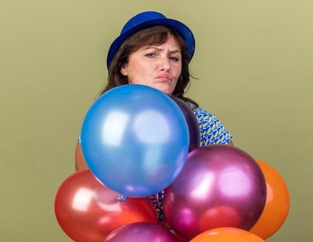 Frau mittleren alters in partyhut mit haufen bunter luftballons mit stirnrunzelndem gesicht