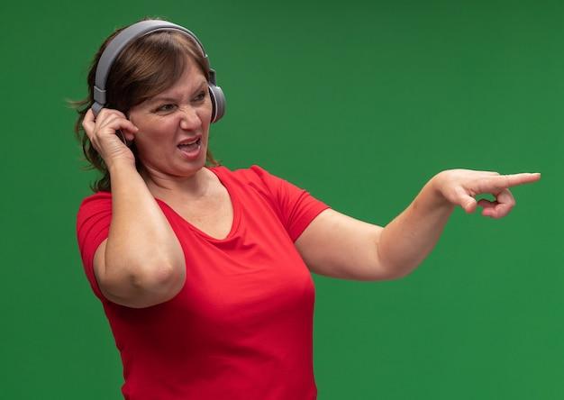 Frau mittleren alters in rotem t-shirt mit kopfhörern, die beiseite schauen, unzufrieden zeigen mit zeigefinger auf etwas, das über grüner wand steht