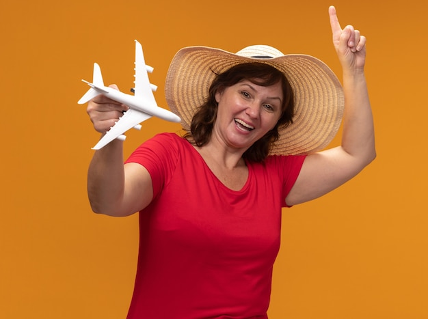 Frau mittleren alters in rotem t-shirt und sommerhut, die spielzeugflugzeug glücklich und aufgeregt zeigt, mit idex finger oben stehend über orange wand