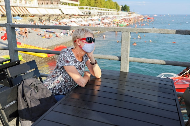 Frau mittleren alters in schutzmaske sitzt tisch draußen am strandpier