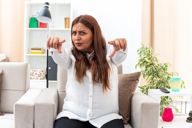 Frau mittleren alters in weißem hemd und schwarzer hose, die mit den zeigefingern nach vorne zeigt und mit ernstem stirnrunzeln auf dem stuhl im hellen wohnzimmer sitzt