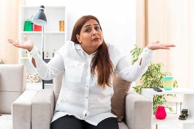 Frau mittleren alters in weißem hemd und schwarzer hose, die verwirrt aussieht und die arme zu den seiten ausbreitet, die auf dem stuhl im hellen wohnzimmer sitzen