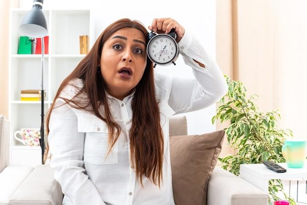 Frau mittleren alters in weißem hemd und schwarzer hose mit wecker, die überrascht und erstaunt auf dem stuhl im hellen wohnzimmer sitzt