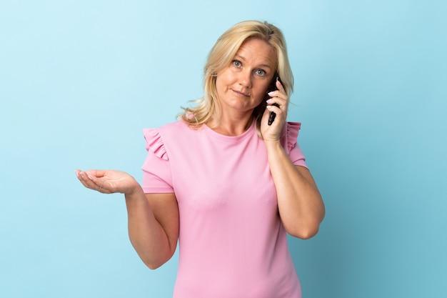 Frau mittleren alters isoliert auf blauer wand, die ein gespräch mit dem mobiltelefon mit jemandem hält