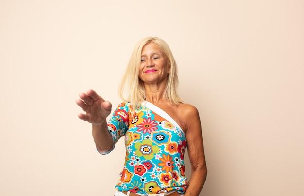 Frau mittleren alters lächelt, begrüßt sie und bietet einen handschlag an, um einen erfolgreichen deal abzuschließen