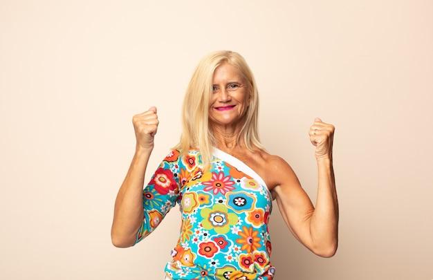 Frau mittleren alters lächelt freudig und sieht glücklich aus, fühlt sich sorglos und positiv mit beiden daumen nach oben
