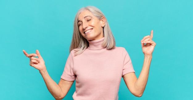 Frau mittleren alters lächelt, fühlt sich sorglos, entspannt und glücklich, tanzt und hört musik, hat spaß auf einer party