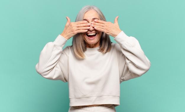 Frau mittleren alters lächelt und fühlt sich glücklich, bedeckt die augen mit beiden händen und wartet auf eine unglaubliche überraschung