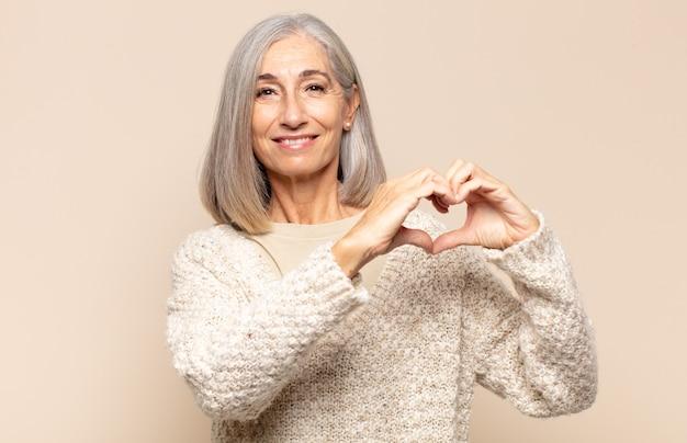 Frau mittleren alters lächelt und fühlt sich glücklich, süß, romantisch und verliebt, macht herzform mit beiden händen