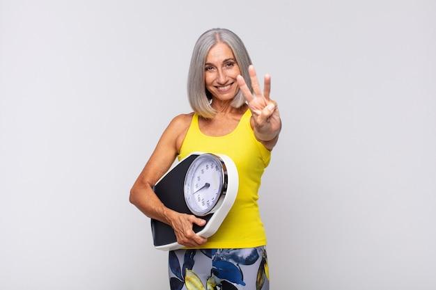 Frau mittleren alters lächelt und sieht freundlich aus und zeigt nummer drei oder drei mit der hand nach vorne