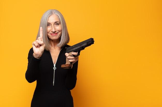 Frau mittleren alters lächelt und sieht freundlich aus, zeigt die nummer eins oder die erste mit der hand nach vorne und zählt herunter
