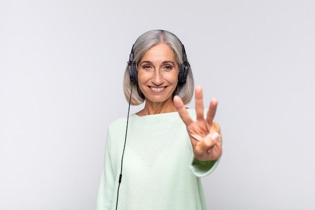 Frau mittleren alters lächelt und sieht freundlich aus, zeigt nummer drei oder drei mit der hand nach vorne und zählt herunter. musikkonzept