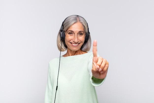 Frau mittleren alters lächelt und sieht freundlich aus, zeigt nummer eins oder zuerst mit der hand nach vorne, zählt herunter. musikkonzept
