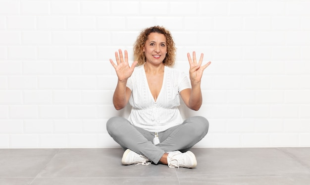 Frau mittleren alters lächelt und sieht freundlich aus, zeigt nummer neun oder neun mit der hand nach vorne und zählt herunter