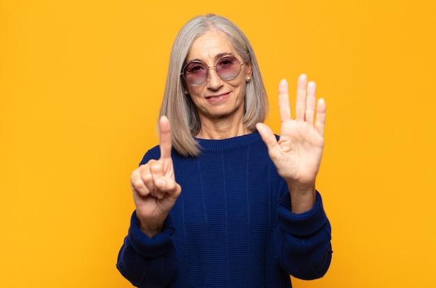 Frau mittleren alters lächelt und sieht freundlich aus, zeigt nummer sechs oder sechst mit der hand nach vorne und zählt herunter