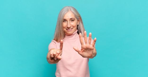 Frau mittleren alters lächelt und sieht freundlich aus, zeigt nummer sechs oder sechste mit der hand nach vorne und zählt herunter