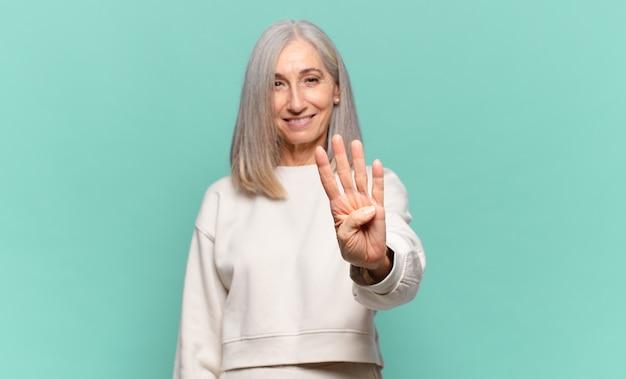 Frau mittleren alters lächelt und sieht freundlich aus, zeigt nummer vier oder vier mit der hand nach vorne und zählt herunter
