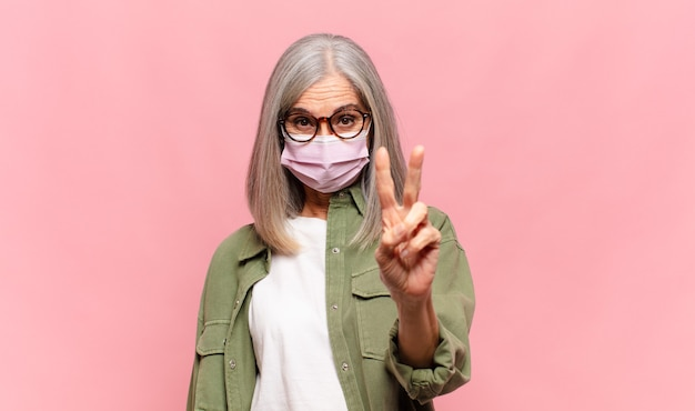 Frau mittleren alters lächelt und sieht freundlich aus, zeigt nummer zwei oder sekunde mit der hand nach vorne und zählt herunter