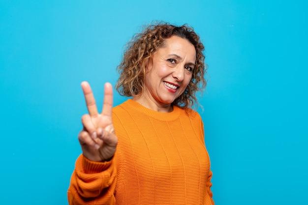 Frau mittleren alters lächelt und sieht glücklich, sorglos und positiv aus, gestikuliert sieg oder frieden mit einer hand