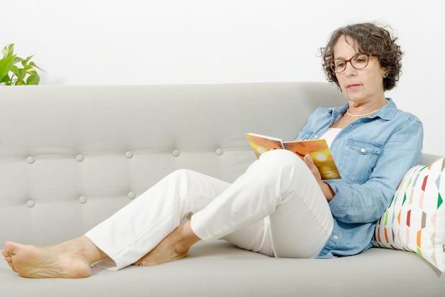 Frau mittleren alters liest, auf dem sofa sitzend