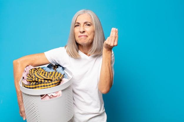 Frau mittleren alters macht capice oder geldgeste und fordert sie auf, ihre schulden zu bezahlen!