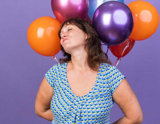 Frau mittleren alters mit einem haufen bunter luftballons glücklich und erfreut lächelnd fröhlich feiern geburtstagsfeier stehend über lila wand