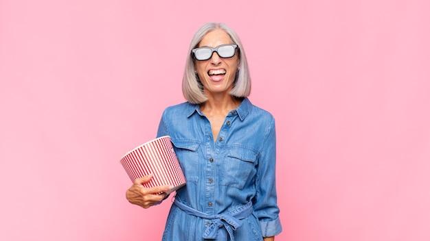 Frau mittleren alters mit fröhlicher, sorgloser, rebellischer haltung, scherzend und herausstreckender zunge, spaßfilmkonzept habend