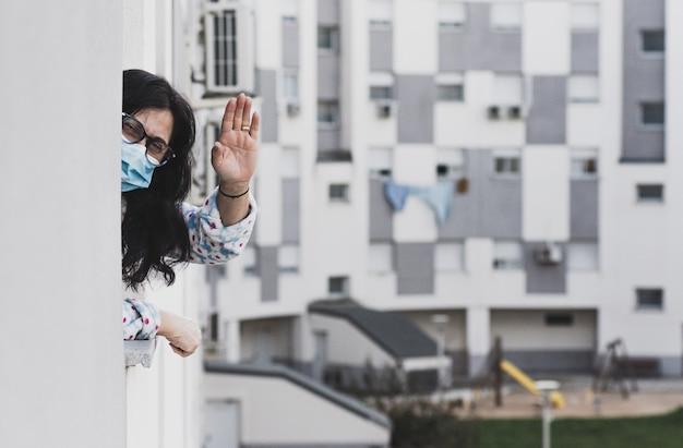 Frau mittleren alters mit gesichtsmaske, die jemandem von ihrem fenster winkt. zu hause isoliert. hintergrund von wohngebäuden.