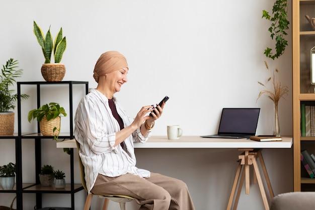 Frau mittleren alters mit hautkrebs, die zeit zu hause verbringt