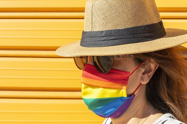 Frau mittleren alters mit hut, sonnenbrille und regenbogenfarbener schutzmaske. lgtb auf gelbem hintergrund. covid-19-konzept