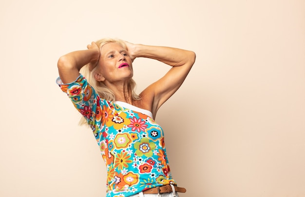 Frau mittleren alters mit offenem mund, die wegen eines schrecklichen fehlers entsetzt und schockiert aussieht und die hände zum kopf hebt