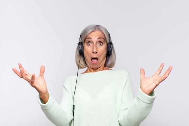 Frau mittleren alters mit offenem mund und erstaunt, schockiert und erstaunt über eine unglaubliche überraschung. musikkonzept