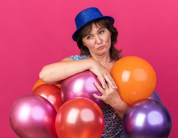Frau mittleren alters mit partyhut, die bunte luftballons hält und mit skeptischem ausdruck beiseite schaut