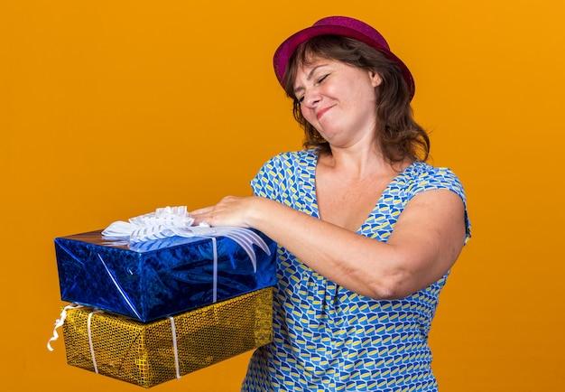Frau mittleren alters mit partyhut, die geburtstagsgeschenke hält, die verwirrt aussehen