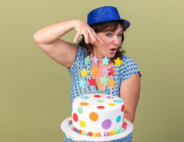 Frau mittleren alters mit partyhut, die geburtstagstorte hält, die fröhlich lächelt und die geburtstagsfeier feiert, die über grüner wand steht