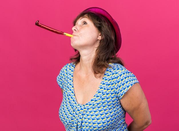 Frau mittleren alters mit partyhut, die pfeife bläst, die verwirrt aufblickt und geburtstagsfeier feiert, die über rosa wand steht?