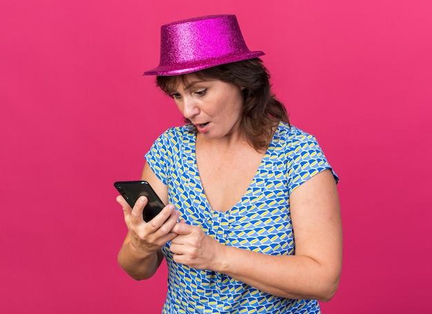Frau mittleren alters mit partyhut, die überrascht auf den bildschirm ihres smartphones schaut
