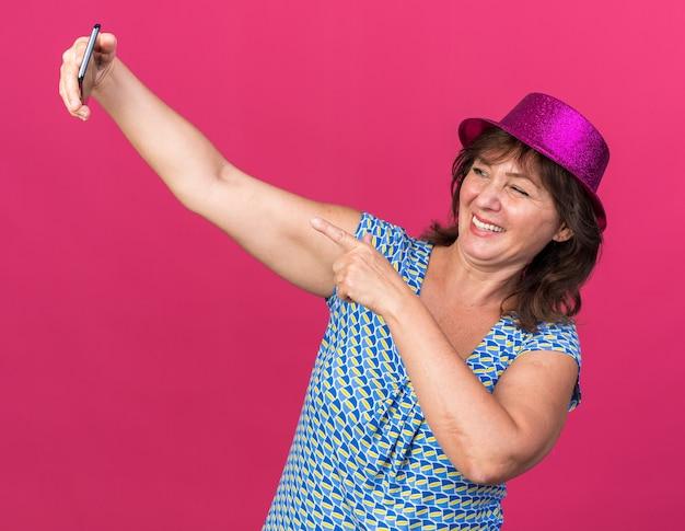 Frau mittleren alters mit partyhut macht selfie mit smartphone glücklich und fröhlich lächelnd und zwinkernd