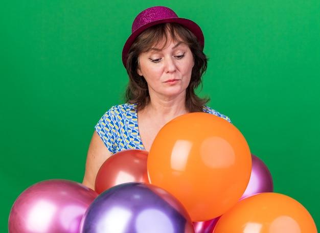 Frau mittleren alters mit partyhut mit bunten luftballons, die fasziniert nach unten schauen und geburtstagsfeier feiern, die über grüner wand steht