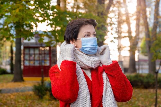 Frau mittleren alters mit schützender medizinischer maske auf ihrem gesicht geht im herbstpark