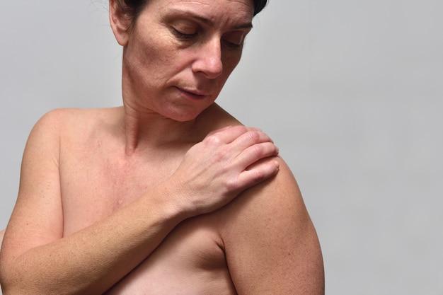 Frau mittleren alters mit schulterschmerzen